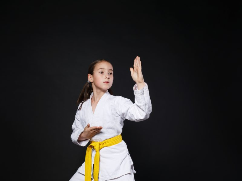 Little girl in karate suit kimono in studio at black background. Female child shows judo or karate stans in white uniform with yellow belt. Individual martial art sport for kids. Waist up portrait